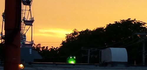 A creepy carnival frog watched the fest over the police building.