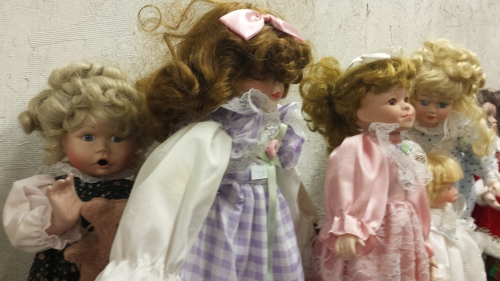 Doll on the left is frozen in the moment of being about to shove the doll to her right off the shelf.