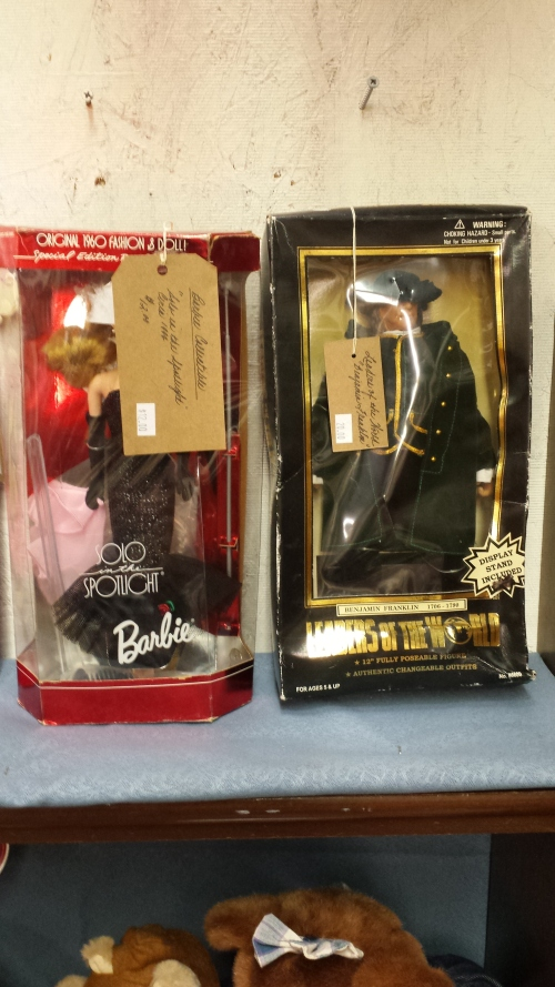 "At left, ""Solo in the Spotlight"" Barbie. At right, ""Leaders of the World"" action figure of Benjamin Franklin, a ""fully poseable figure"" with ""authentic changeable outfits."""