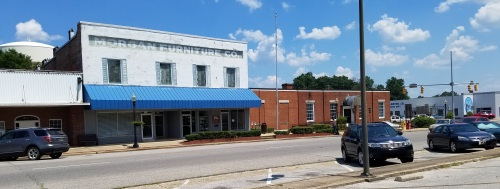 A view of the east side of Alabama Avenue while standing on east side of Old Courthouse. The two-story building was once the millinery shop owned by Truman Capote's Faulk relatives. The brick one-story to the right (south) is the post-office, dating to 1937. According to a book written by Monroe County Heritage Museums, the post office was on the south side of the courthouse square before 1937.