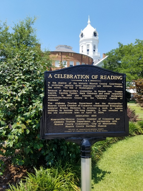 A sign near statues of children reading, south of Old Courthouse.